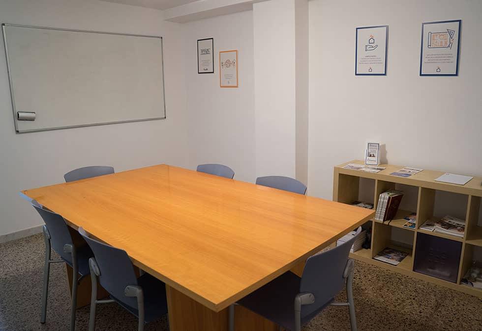 sala de juntes, amb la taula de juntes i l'estanteria al fons