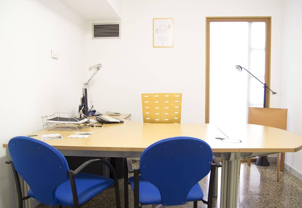 Fotografia de la sala de rebre visites del Hub Terrassa. Te una taula amb dues cadires de confidents i una altre per a tu (tot i que hi caben fins a 4 persones), calefacció i aire acondicionat i wifi.